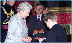 The Queen presents a silver medal to Thomas, aged 12, from London