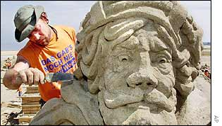 US artist Daniel Clover carves a sand figure of German pirate Klaus Stoertebecker