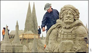 Sand sculpture with sand church in the background