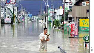A man holds his dog on a flooded street in Oogaki, central Japan
