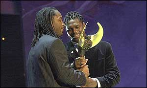 Lennox Lewis (left) receives an award from Audley Harrison (right)