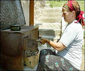 Ibrima Oric cooks a meal outside her ruined home