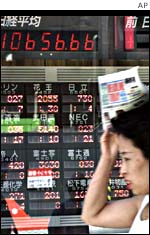 A woman walking past a board showing Tokyo Stock Exchange data