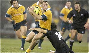 Australia's Chris Latham is tackled by Doug Howlett