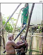 Villagers shoring up flooded home