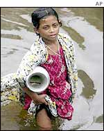 Girl wades through flooded streets looking for drinking water