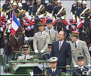 French President Jacques Chirac (in suit) stands on a command car to review troops in the parade