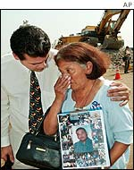 A mother carrying a picture of her son is comforted