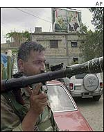 A Palestinian carries a rocket-propelled grenade while on patrol in Ayn al-Hilweh