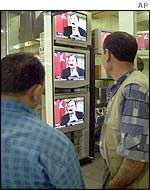 Turkish men watch television at an electronics market in Istanbul as Turkey's ailing Prime Minister Bulent Ecevit gives a TV interview