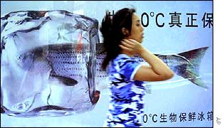 A Chinese woman walks past an advertisement showing a fish encased in ice on the streets of Beijing