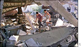 Palestinian children pick through rubble of building destroyed by Israeli warplanes