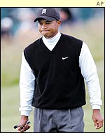 Tiger Woods purses his lips as he walks down the fairway