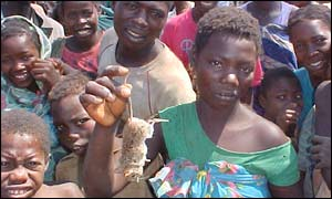 Woman holds a rat in Angola