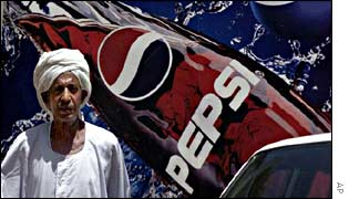 A Sudanese man in front of a Pepsi hoarding in Khartoum