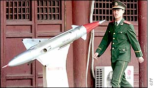 A Chinese soldier walks past an old missile