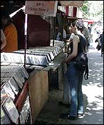 Belgrade teens shopping at a kiosk for pirate CDs