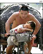 A man cycles with his child in Beijing