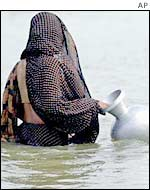 Bangladeshi woman wades through flood water