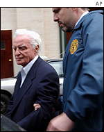 John Rigas is led from New Yorks main post office building by US postal inspector police.