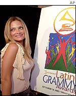 Chilean singer Nicole pauses by a poster of the 3rd Annual Latin Grammy Awards during the nomination news conference in Beverly Hills Wednesday, July 24, 2002