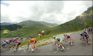 The cyclists of the 89th Tour de France round a curve in a downhill during the 17th stage