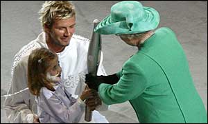 The Queen receives the Commonwealth baton from Kirsty Howard and David Beckham