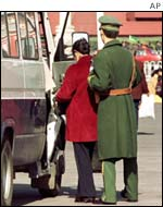Police escort a sect member away from Tiananmen Square
