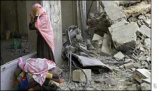 Palestinian woman looks at rubble of building destroyed in Tuesday's air strike