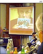 Press and officials watch a video link with Britain, where Alexander Litvinenko (on the screen) said he received a statement from a key suspect in the 1999 blasts
