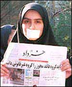 Woman protester with tape over her mouth holds reformist newspaper