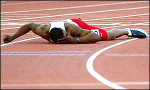 Mark Lewis-Francis lies flat on the track after what looks to be a hamstring problem  ends his 100m gold hopes