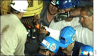 Miner is helped out of rescue capsule by emergency workers at the scene