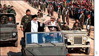 Ayatollah Ali Khamenei waves to soldiers from a jeep