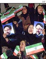 Iranian girls wave pictures of Mohammad Khatami