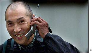 A Japanese passer by speaking on a mobile phone