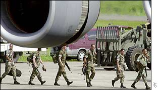 US troops walk under the engine of a plane that will take them out of the Philippines