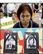 A woman prays above photos of the two dead girls