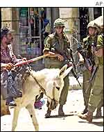 A Palestinian on his donkey  passes  Israeli soldiers at a road block in Hebron
