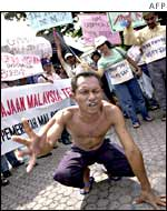 A migrant worker protests outside the Malaysian embassy in Jakarta