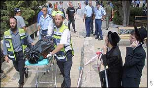 Two ultra-orthodox Jews look on as a victim is taken away from the scene of a bombing at a student cafeteria in Jerusalem
