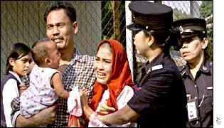 Police arrest a woman and her family outside a UN office