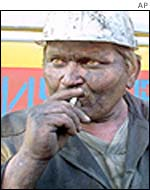 A miner smokes as he watches the rescue works at the Zasyadko mine