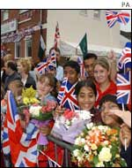 Crowds of school children greet the Queen outside the mosque