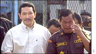Tommy Suharto walks with a prison guard