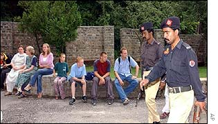Pakistan police pass by the frightened foreign students