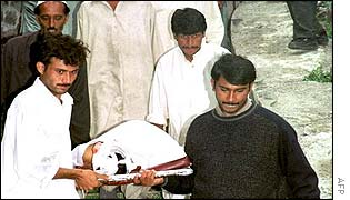 Rescue workers carry a dead body out of the morgue at Murree hospital