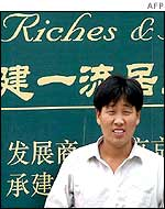 Man in front of a property sign in Shanghai