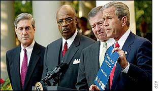 US President George W Bush [r] holds pamphlet as others, including FBI Director Robert Mueller, look on