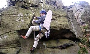 Man abseiling with ironing board on his back